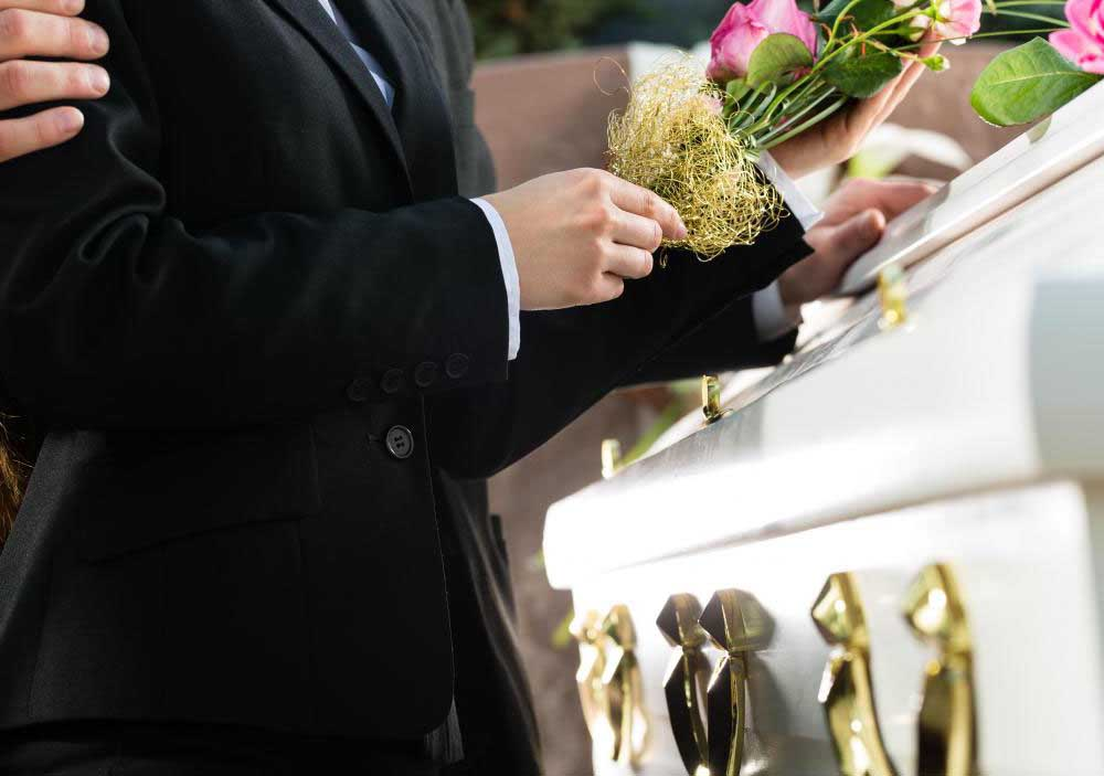 images/nadejda/man-in-suit-with-flowers-at-white-casket.jpg
